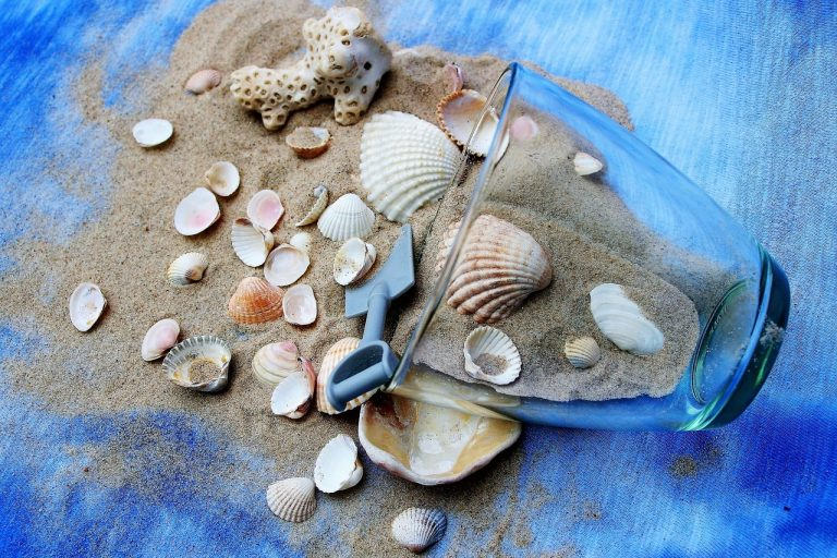 sand and shells with tipped over vase