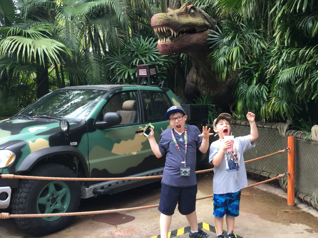 Two boys pretending to be scared of a T-Rex at Universal Studios Orlando