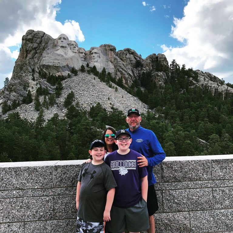 A mom, dad and two sons stand in front of Mount Rushmore