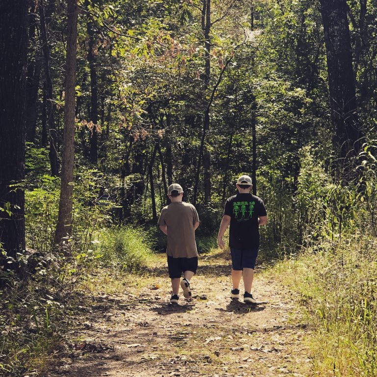two boys walking a wooded trail in pea ridge national military park