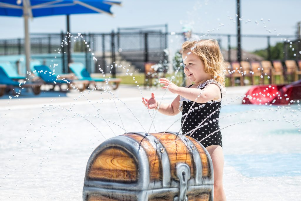 toddler with water spraying trunk at waterpark