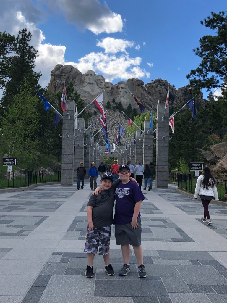 two boys standing in front of the avenue of flags at mount rushmore